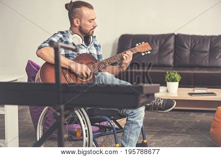 Need good company. Young invalid male person sitting in semi position playing the guitar while keeping his right leg on the left one