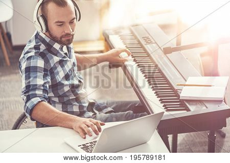 Keen on his work. Confident composer sitting in semi position wearing headphones using laptop while writing new composition