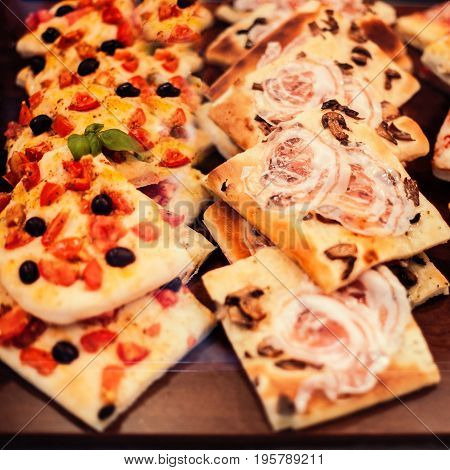 Pizza Take Away pieces on a stall Traditional Italian Focaccia with tomatoes black olives and cheese