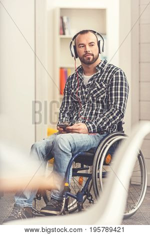 Deep in thoughts. Disabled male sitting in wheelchair looking sideways, wearing headphones