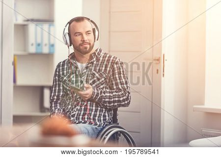 Spend your time with pleasure. Delighted invalid male holding phone in left hand keeping smile on his face while listening to music