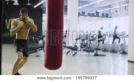 Boxer training punching bag in fitness studio