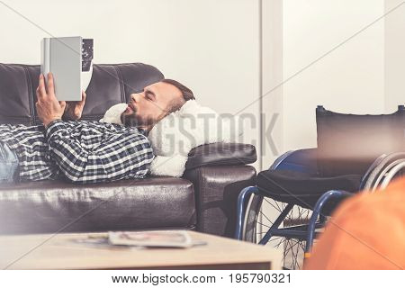 Look at it. Handsome man paging his book lying on the sofa, keeping his wheelchair near coach