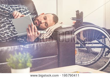 Day sleep. Attractive bearded male person reading his book while lying on the sofa, keeping his wheelchair near sofa