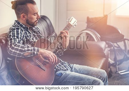 Relax with music. Serious bearded musician sitting on the black leather coach looking at his fingers while holding instrument
