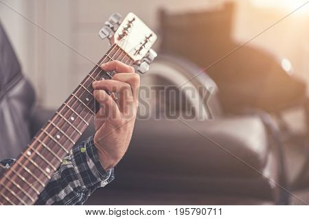 Sing this song. Photo of male hand keeping fingers on the guitar, wearing checked shirt while sitting on the coach