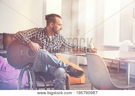 Dictate me that song. Attractive bearded man being on the wheelchair keeping guitar on legs while making notes