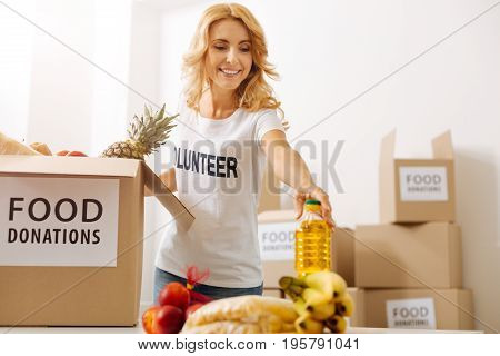 Fit everything. Admirable hardworking charismatic lady taking a bottle of oil for packing it in a box shipping it to those in need