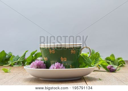 Green Cup With Saucer. Fresh Mint Leaves And Clover Flowers For Making Herbal Tea.  Wooden Backgroun