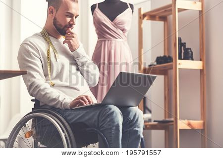 Let me create. Invalid designer sitting before dummy, looking at screen of his computer while touching his chin