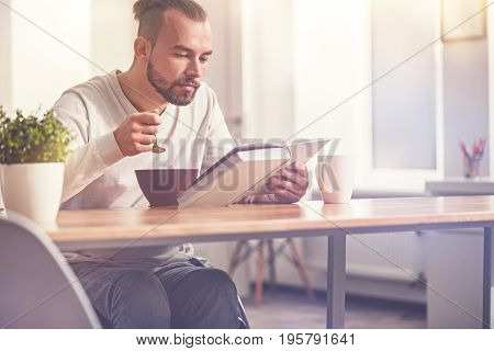 Enjoy your meal. Serious male person holding spoon in the air while reading interesting book, bowing his head