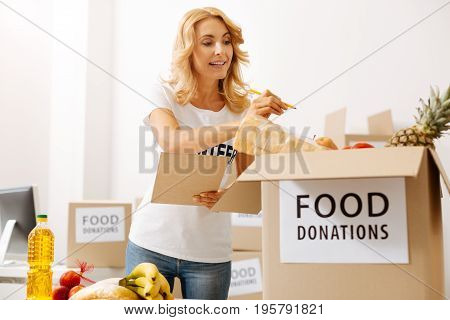 Exact number. Admirable devoted productive lady holding a list she checking with for making sure she not missing anything in the package
