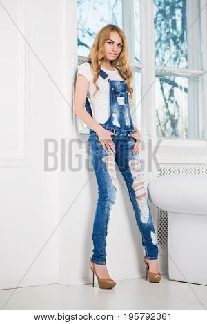 Young pretty woman posing in ragged denim overalls near the window