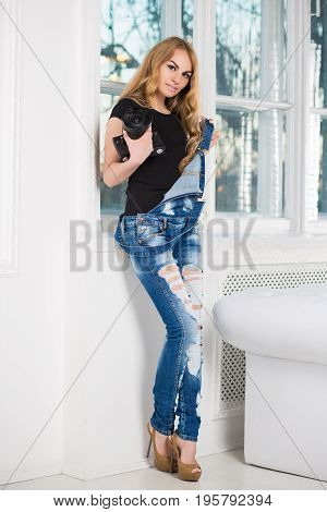 Cute blond woman wearing ragged denim overalls posing with camera