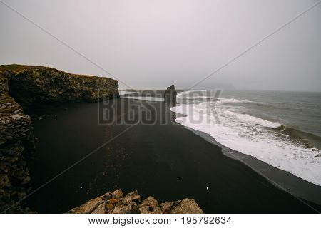 Black beach Kirkjufjara during the storm on Atlantic ocean.