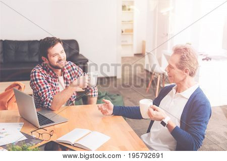 Have a break. Cheerful delighted colleagues drinking coffee and sitting at the table while having a break in the office