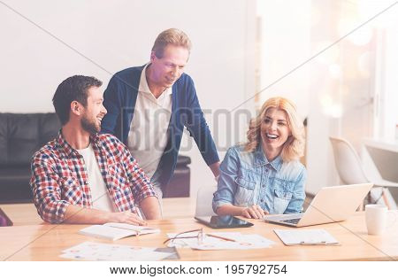 Do you need my help. Senior professioanl worker standing near table while helping his young colleagues and working in the office