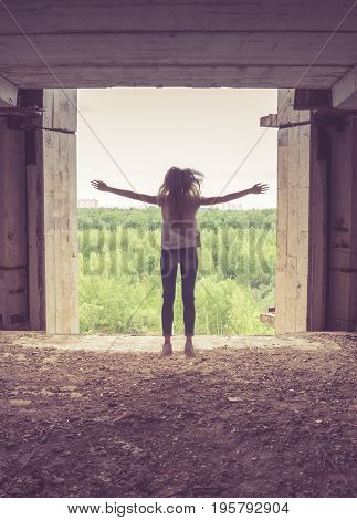 Silhouette of a girl trying to jump out of a window of a ruined building in a green forest outside. Russia