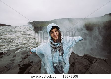 Young joyful hiker female smiling near Dettifoss waterfall in Vatnajökull National Park in Northeast Iceland.Tourist visiting Iceland and touring through ring road.Exploring.Nature photographer.