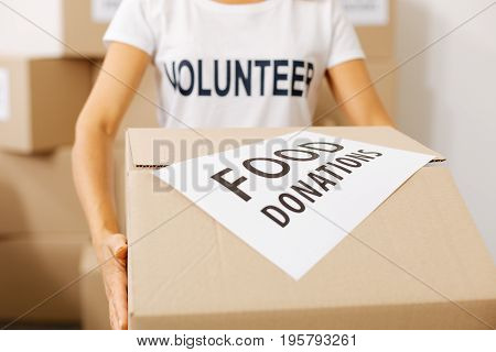 Important package. Diligent committed smart lady working for charity institution pro bono and collecting food supplies for those in need while carrying a box