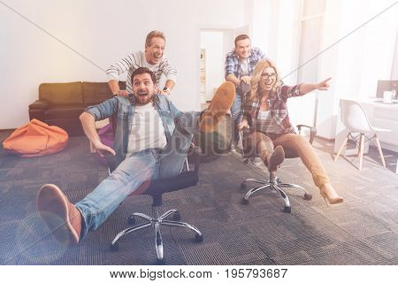 Follow this way. Cheerful smiling colleagues sitting in office chairs and riding while having a break