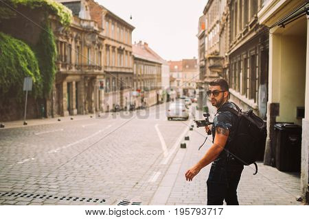 Male professional videographer travel photographer making video in 4K resolution trough the streets of Zagreb holding stabilizer.Filming with stabilized camera.Travel light equipment