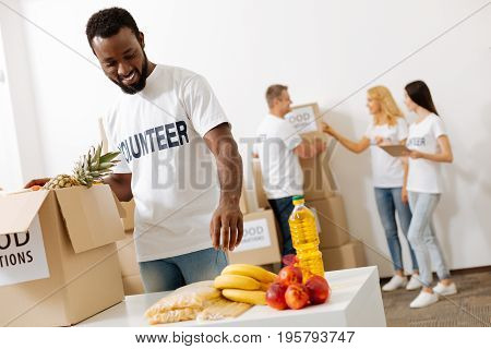 Large handed. Charismatic optimistic smart guy putting some fruits in the box while working pro bono and shipping parcels to those in need