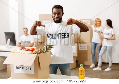 Helping the world. Handsome altruistic bright man dedicating his free time to a good cause and helping packing parcels with food supplies for those in need