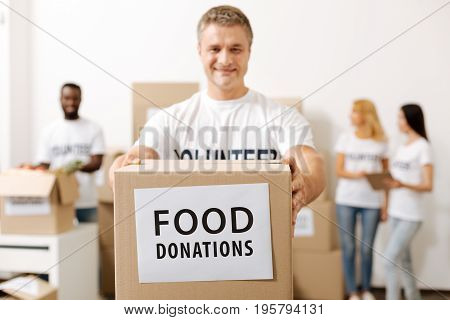 Take it out. Handsome altruistic strong man holding a box he shipping to those in need while working as a volunteer