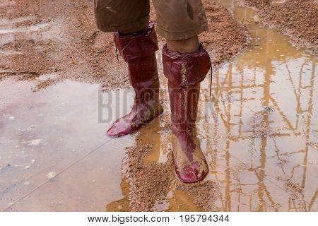 Galoshes man going in rubber boots in a meadow
