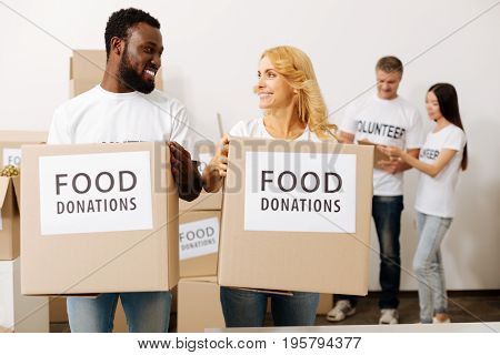 Positive atmosphere. Charming friendly sincere men and women working in charity foundation and carrying boxes with supplies while enjoying good time