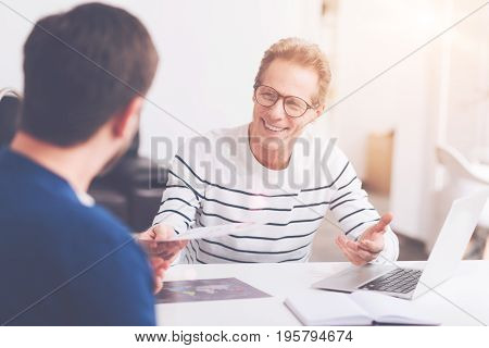 Well done. Cheerful professional senior man sitting at the table and approving project of his younger colleague while working in the office