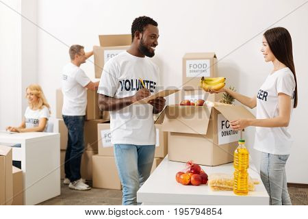 Check before shipment. Handsome dedicated lively man managing the contents of the parcels and making sure nothing being missed while talking to his colleague