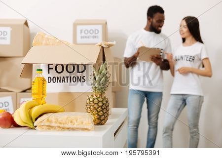 Helping each other. Inspiring pretty motivated woman working for charity foundation and packing boxes with food for the poor while talking to her colleague