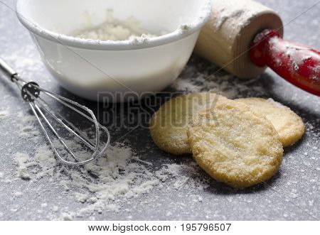 Crisp sugar cookies are surrounded by flour and cooking utensils on this dark gray countertop. The cookies have a fantastic texture that lets the viewer know they are crunchy.