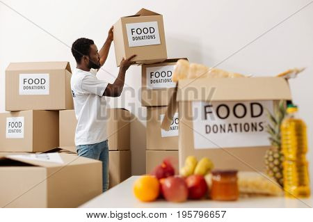 Examining the packing. Handsome determined altruistic guy moving the boxes with food people donating while preparing a weekly shipment for those in need
