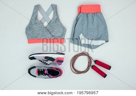 Top View Of Sportswear With Sneakers And Skipping Rope Isolated On Grey