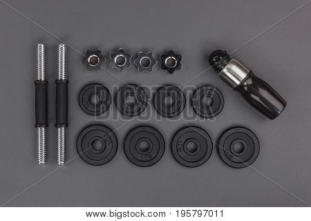 Top View Of Various Metal Barbells And Weights With Shaker Isolated On Grey
