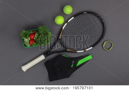 Top View Of Tennis Racquet And Balls, Sportswear, Fitness Tracker And Healthy Vegetable Salad