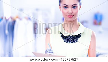 Young fashion designer working at studio , standing with folder