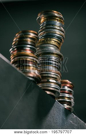 Selective Focus Of Stacks Of Different Coins Standing On Edge Of Table