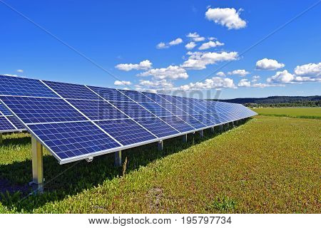 Solar panel on field. Clear blue sky with a few small clouds on background. Horizontal image with space for text.