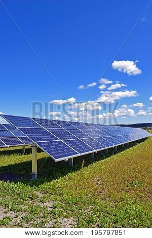Solar panels on field. Clear sky with a few small clouds on background. Vertical image.