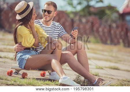 happy multiethnic couple listening music with earphones on smartphone while sitting on skateboard in city