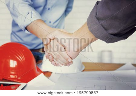 Two confident business man shaking hands during a meeting in the architect office success dealing greeting and partner concept.
