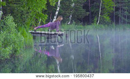 Young woman doing yoga exercises on the lake shore. Chaturanga dandasana