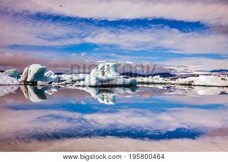 The luminous icebergs on Jokulsarlon, Iceland. The concept of extreme northern tourism. Striped clouds beautifully reflected in the smooth water of lagoon