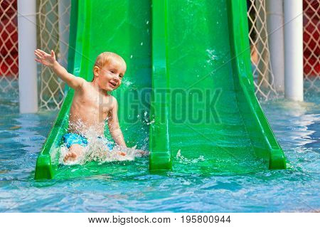 Funny happy baby boy have fun sliding with splashes in blue swimming pool. Family summer lifestyle children with parents water sports activity in aqua park on holidays.