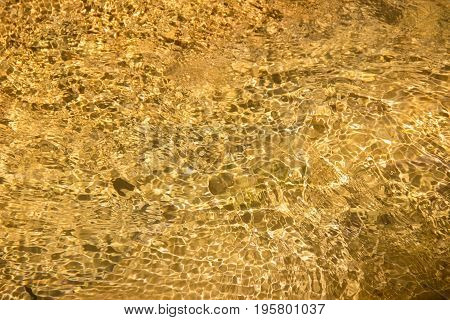 The texture of transparent water with patches of yellow stone in strengthening the Sunlight