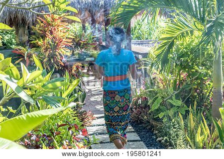 BALI, INDONESIA - JANUARY 21, 2017: Balinese women in traditional batik kebaya walking with offering in a tropical garden.
